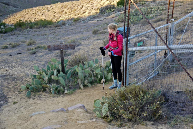 A girl backpacker standing by the sign of Trans-Catalina Trail